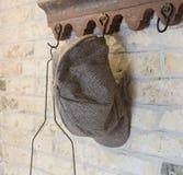 垂悬在挂衣架的老农夫帽子 免版税库存图片