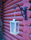 垂悬在日志墙壁上的木烛光 免版税库存照片