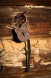 垂悬在日志墙壁上的老,开锁的挂锁 免版税库存图片