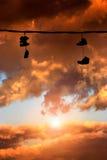 垂悬在日落的运动鞋 免版税库存照片