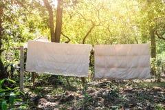垂悬在晒衣绳的两条白色毯子烘干下午太阳在乡下,泰国 免版税库存图片