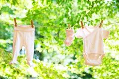 垂悬在晒衣绳的婴孩衣裳 库存照片