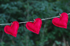 垂悬在晒衣绳的三明亮的红色心脏户外 免版税库存图片