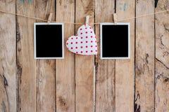 垂悬在晒衣绳绳索的白色心脏和两张照片框架与 库存图片