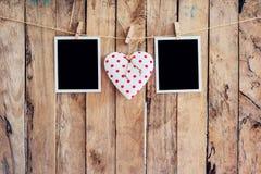 垂悬在晒衣绳绳索的白色心脏和两张照片框架与 免版税库存图片