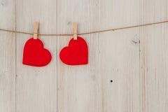 垂悬在晒衣绳的红色心脏 在老木头background.valentines日主题 免版税库存图片