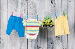 垂悬在晒衣绳的婴孩衣裳。 库存图片