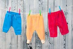 垂悬在晒衣绳的婴孩衣裳。 免版税库存照片