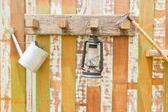 垂悬在木墙壁上的园艺工具 免版税库存照片