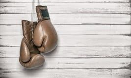 垂悬在木墙壁上的拳击手套 免版税库存图片