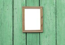 垂悬在木墙壁上的空的木制框架 免版税库存图片