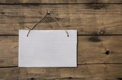 垂悬在木墙壁上的老白色标志 免版税库存照片