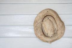 垂悬在木墙壁上的老被编织的帽子 库存照片