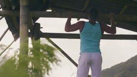 垂悬在木标志横线训练吸收肌肉的体育人室外 在单杠的男性吸收锻炼 后面看法运动员 股票录像