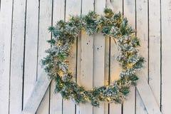 垂悬在木盾的圣诞节花圈 库存照片