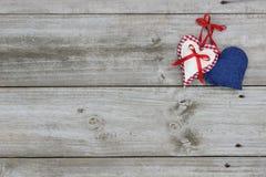 垂悬在木背景的红色,白色和蓝色心脏 免版税图库摄影