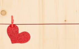 垂悬在木背景,情人节的概念的一装饰红色心脏 库存照片