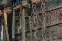 垂悬在木被构筑的棚子或谷仓墙壁上的园艺工具 免版税库存照片