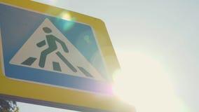 垂悬在杆的一个行人交叉路标志反对天空蔚蓝和明亮的太阳 公路安全概念 股票录像