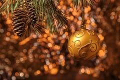 垂悬在杉木的发光的圣诞节金球分支有橙色背景 图库摄影