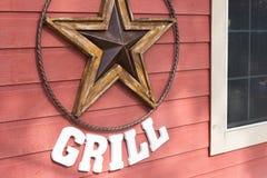 垂悬在格栅地方的木墙壁上的生锈的金属星标志 免版税图库摄影