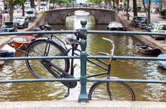 垂悬在桥梁栏杆的老被放弃的自行车在阿姆斯特丹 免版税库存照片