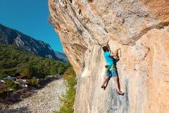 垂悬在森林和村庄上的岩石的成熟登山人 图库摄影