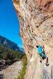垂悬在森林和村庄垂直上的岩石的成熟登山人 库存照片