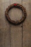 垂悬在橡木板条门的简单的圣诞节枝杈花圈 免版税库存图片