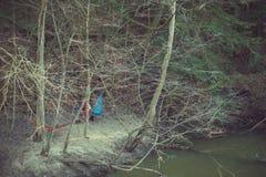 垂悬在河岸的五颜六色的吊床在森林 免版税库存图片