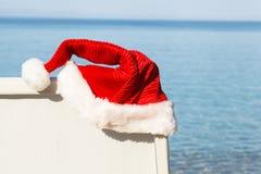 垂悬在海滩睡椅的圣诞老人帽子。 库存照片