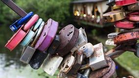 垂悬在湖背景的一座桥梁的多彩多姿的挂锁 库存照片
