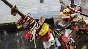 垂悬在湖背景的一座桥梁的多彩多姿的挂锁 免版税库存照片