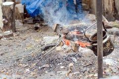 垂悬在火附近的水壶在森林里 库存照片
