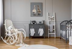 垂悬在灰色木洗脸台的瘤的婴孩衣裳在可爱的托儿所、拷贝空间和海报在空的墙壁上 免版税库存照片