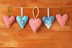 垂悬在灰色木背景的红色心脏 免版税图库摄影