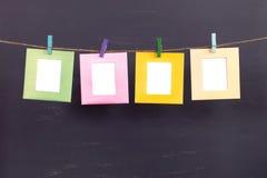 垂悬在灰色背景的绳索的四个框架 免版税库存照片