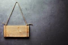 垂悬在灰色织地不很细墙壁上的绳索的木牌 免版税库存照片