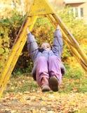 垂悬在爬升套架的微笑的女孩 免版税库存图片