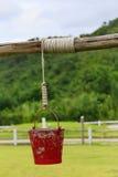 垂悬在牧场地的红色桶 库存照片