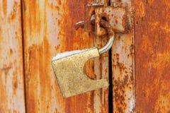 垂悬在生锈的门的开放老挂锁 库存图片
