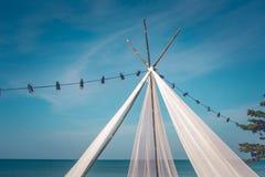 垂悬在电导线的沙子电灯泡海滩和行的白色亭子有美好的海景视图和蓝天 库存照片