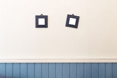 垂悬在白色和蓝色墙壁上的两个小方形的框架 库存照片