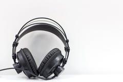 垂悬在白色墙壁上的耳机 背景是能使用的不同的例证音乐目的 音频黑暗的设备闪电晚上 免版税库存照片