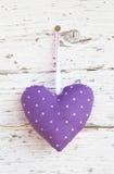 垂悬在白色木表面o上的浪漫被加点的心脏形状 免版税库存图片