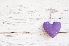 垂悬在白色木表面o上的浪漫被加点的心脏形状 免版税图库摄影