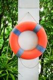 垂悬在白色混凝土的橙色救生浮游物 免版税库存照片