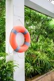 垂悬在白色混凝土的橙色救生浮游物 免版税图库摄影