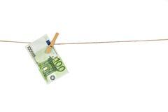 100垂悬在白色背景的晒衣绳的欧元钞票 免版税库存照片