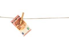 10垂悬在白色背景的晒衣绳的欧元钞票 图库摄影